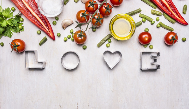 concept of good nutrition, various vegetables, spices and oil, with the word Love border ,place for text  on wooden rustic background top view