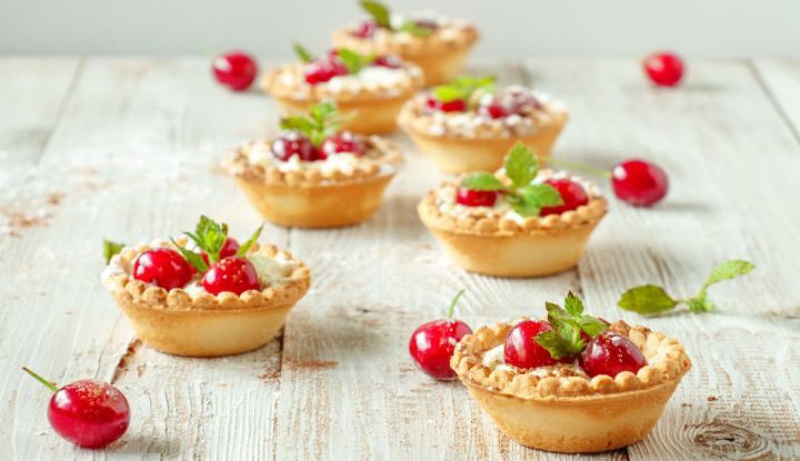 Tartlets with whipped cream and cherry.