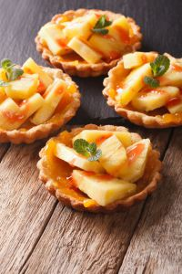 Tartlets with pineapple, jam and mint close-up. vertical